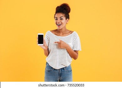 Happy african lady showing smartphone with blank screen and smiling isolated