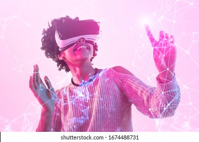 Happy African lady smiling an d touching virtual network while wearing VR headset under pink illumination
