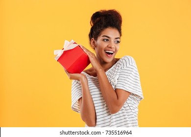 Happy african lady in white shirt looking aside and laughing while holding present isolated