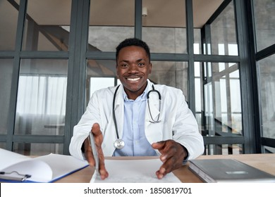 Happy african male doctor talking to camera during telehealth mobile consultation. Black physician consulting patient in virtual telemedicine phone app chat. Tele medicine videocall visit, headshot. - Shutterstock ID 1850819701