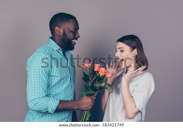 happy african man giving bouquet of roses to his girlfriend