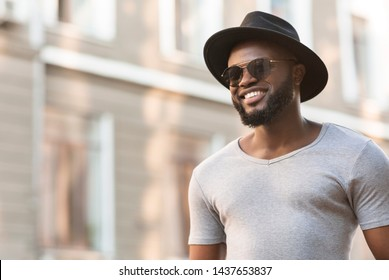 Happy african man in hat walking near the old buildings in the city and widely smiling, panorama, copy space