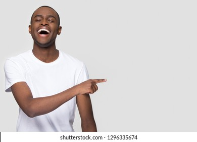Happy african man laughing out loud at funny joke pointing finger aside at copy space, jovial cheerful black guy burst with laughter joy having fun advertising isolated on white studio background