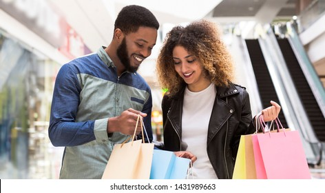 Happy african man showing his girlfriend purchases in shopping bags in mall center, panorama