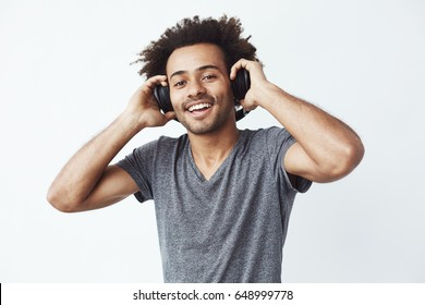 Happy african man smiling listening to music in headphones. White background.
