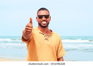 Fröhlicher afrikanischer Mann, der am Strand aufsteht - Gewissener afro-amerikanischer Kerl, der Geste zustimmt, lächelt auf blauem Hintergrund - Konzept der positiven Zustimmung , Vertrauen oder Zustimmung - Bild