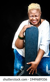 Happy african mature woman posing in studio with a guitar