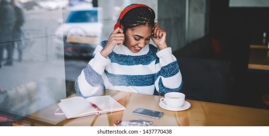 Happy african meloman enjoying favourite positive music playlist via bluetooth headphones sitting with textbook for writing during coffee break, cheerful woman feeling excited from listening radio