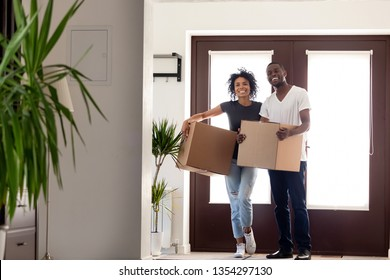 Happy african mixed race couple holding big carton boxes entering modern house standing at doorway, millennial husband and wife moving buying own apartment, starting new life, loan or mortgage concept