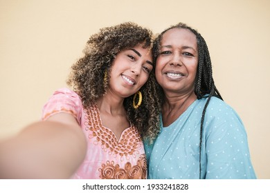 Happy african mother and adult daughter taking a selfie with smartphone while wearing traditional dress - Black people and family love concept