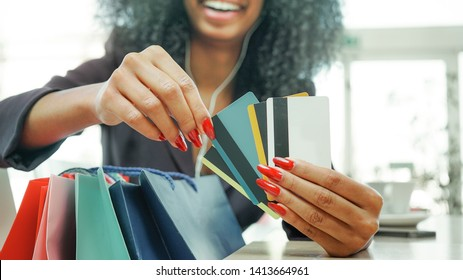 happy african origin girl at shopping mall  holding many credit cards and shopping bags.