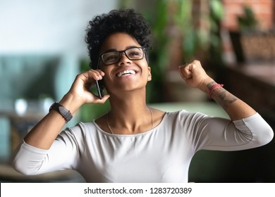 Happy african rewarded businesswoman laughing with joy, excited black student talking on mobile phone with best friend share news about getting internship or dream job received highest honors in study