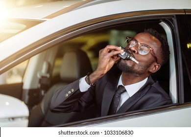 happy african vehicle buyer inside his new car kiss him car key