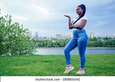 happy african woman afro braids dreadlocks wearing jeans with arms outstretched body positive summer lake street