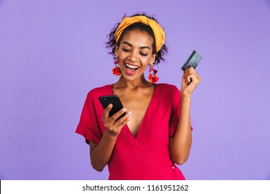 Happy african woman in dress using smartphone while holding credit card over purple background