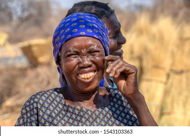 Happy African woman, laughing, wearing a blue scarf in a village in Botswana , sunny day