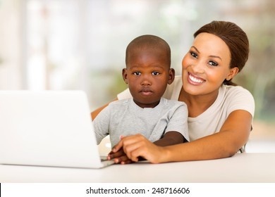 happy african  woman relaxing at home with her little boy