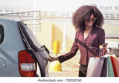 happy african woman with shopping bags opening car