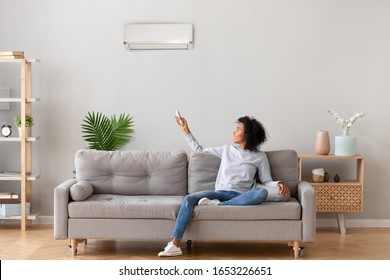 Happy african woman sitting on sofa holding remote control switching on air conditioner, black lady relax on couch set comfort cool fresh ventilation in living room, domestic climate system appliance