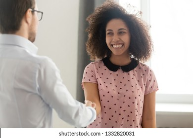 Happy african woman student intern worker getting appreciated rewarded hired promoted handshaking boss congratulating black employee with recognition shaking hands expressing gratitude and respect