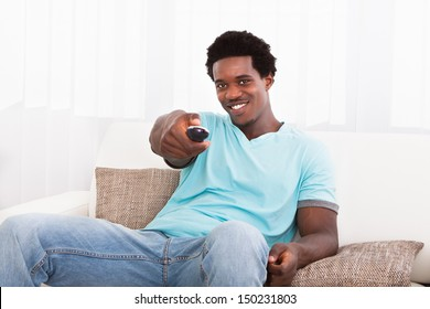 Happy African Young Man Watching Television At Home