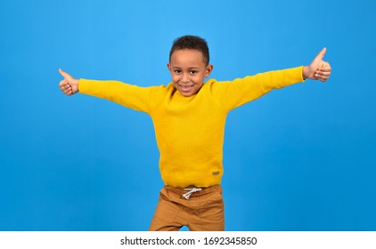 Happy African-American boy rejoices and smiles at victory or achievement, raises his hands up, on a blue studio homogeneous background. concept of winning, achieving the goal of striving to win.