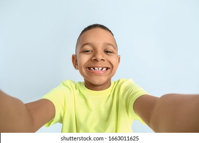 Happy African-American boy taking selfie on color background