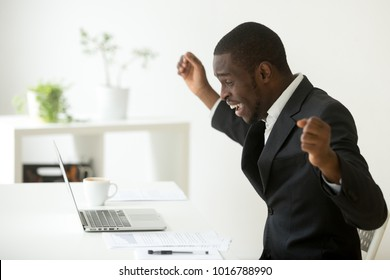 Happy african-american businessman in suit looking at laptop excited by good news online, black man winner sitting at office desk achieved goal raising hands celebrating business success win result
