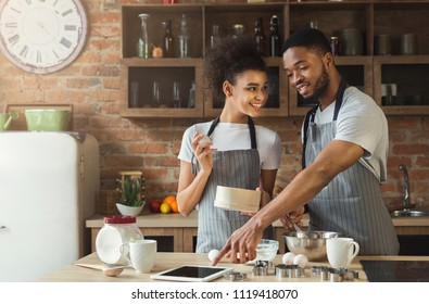 Happy african-american couple baking pie and using digital tablet in loft interior.