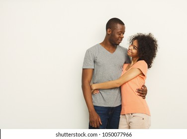 Happy african-american couple in casual embracing and smiling at white studio background, love story, copy space, isolated