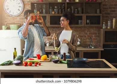 Happy african-american couple cooking healthy food and having fun together in their loft kitchen at home. Woman and man drinking wine. Preparing vegetable salad.