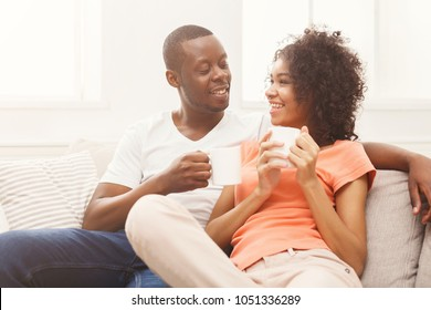 Happy african-american couple drinking coffee at cozy home. Family leisure and relaxation concept, copy space