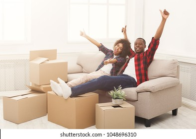 Happy african-american couple unpacking moving boxes and having fun in new apartment. Young family having own home, showing thumbs up, copy space