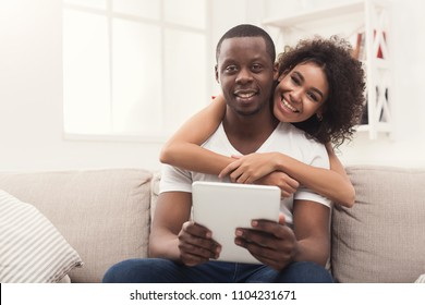 Happy african-american couple using digital tablet, online shopping or networking on sofa at new apartment, copy space