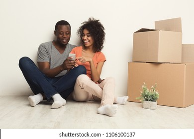 Happy african-american family couple discussing interior design of new apartment, choosing color scheme on smartphone, sitting on floor against white wall near moving and storage boxes, copy space