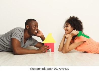 Happy african-american family couple with house and key symbols. Lying on floor against white wall at new appartment. Moving and real estate concept, copy space, isolated