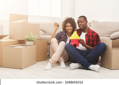 Happy african-american family couple with house and key symbols. Sitting on floor against near storage boxes at new apartment. Moving and real estate concept, copy space, isolated