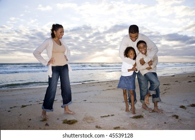 Happy African-American family with two children hugging on beach