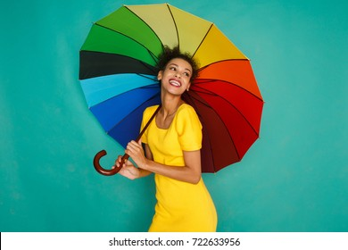 Happy african-american girl in bright yellow dress under rainbow colored umbrella posing at azur studio background, copy space
