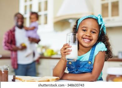 Chúc mừng cô gái người Mỹ gốc Phi với ly sữa nhìn vào máy ảnh trên nền của cha và em gái
