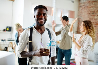Happy African-american guy with drink looking at camer aon background of dancing friends