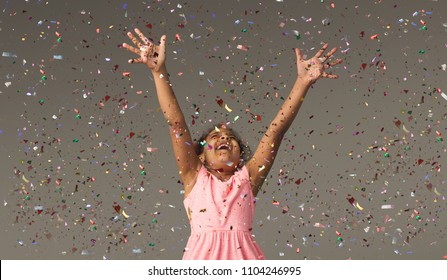 Happy african-american little girl at gray studio background, copy space. Portrait of beautiful child having fun with shiny confetti