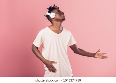 happy African-American man in headphones listening to music on pink background