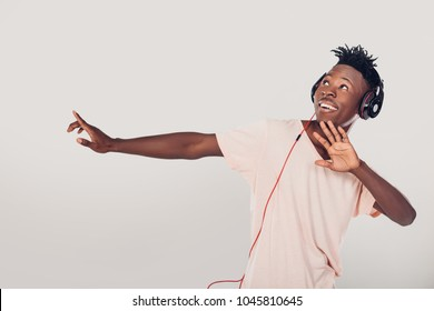 happy African-American man in headphones listening to music on gray background