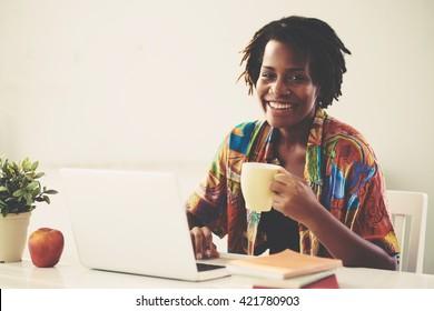 Happy African-American woman having coffee break