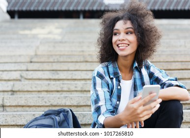 Happy african-american woman messaging on mobile while sitting on concrete steps outdoors. Technology, communication and big city lifestyle concept, copy space