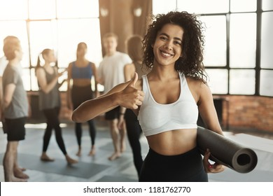Happy african-american woman ready for workout, holding yoga mat and showing thumb up. Fitness and healthy lifestyle recommendation, copy space