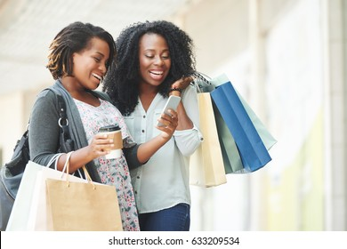 Happy African-American women reading message on smartphone