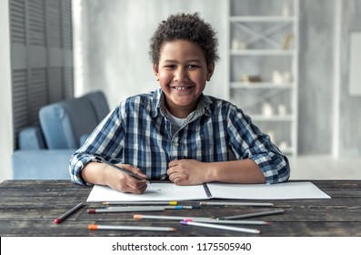 Happy Afro American boy is drawing using colored pencils, looking at camera and smiling while sitting at the table at home