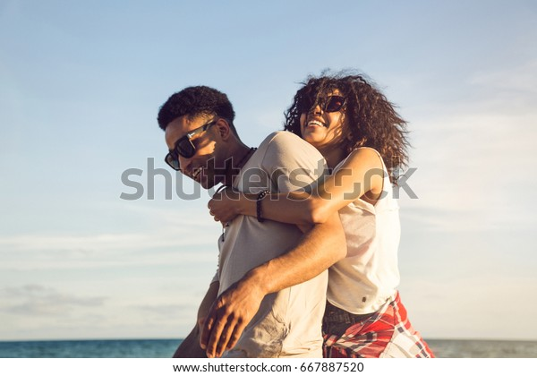 Happy afro american couple having fun together on a beach